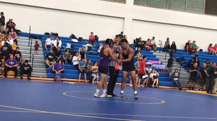 Two wrestlers shaking hands at a tournament on Maui. Photo by Angelika Ramos.