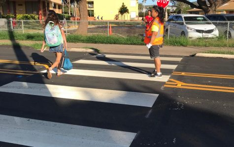 Aunty Ulu helping elementary student cross the street. Photo by Keona Blanks.